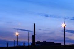 Silhueta de construir a estação subterrânea do armazenamento de gás contra t Foto de Stock Royalty Free
