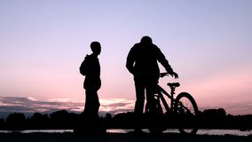 Silhueta de dois adolescentes que comunicam-se no banco ou no lago de rio Os jovens encontram-se no nascer do sol ou no por do so filme