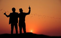 Silhueta de dois povos felizes no por do sol Fotografia de Stock