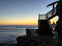Silhueta de dois surfistas que escalam escadas no por do sol ao longo do litoral rochoso Foto de Stock Royalty Free