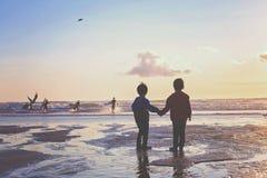 Silhueta de duas crianças, surfistas de observação na praia Fotos de Stock Royalty Free