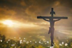 A silhueta de Jesus com cruza sobre o conceito do por do sol para a religião Fotografia de Stock
