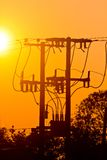 Silhueta de linhas elétricas e de fios bondes do polo no por do sol Foto de Stock Royalty Free