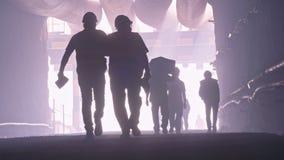Silhueta de muitos trabalhadores da construção que andam para fora de um grande túnel video estoque