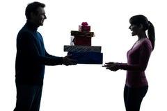 Silhueta de oferecimento dos presentes do Natal do homem da mulher dos pares Foto de Stock Royalty Free