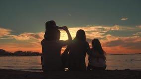 Silhueta de pais novos com as duas crianças que olham o por do sol na praia Povos que têm o divertimento no mar Conceito de vídeos de arquivo
