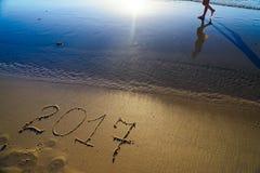 Silhueta de passeio do woman& x27; reflexão de s na praia e no YE novo Imagens de Stock Royalty Free