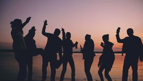 A silhueta de povos novos da dança do grupo tem um partido na praia no por do sol video estoque