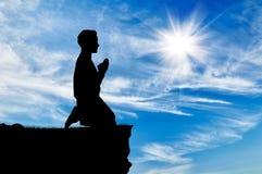 Silhueta de rezar do homem Imagens de Stock