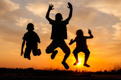 Silhueta de salto de meninos e de meninas felizes no por do sol Fotos de Stock
