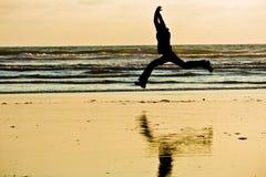 Silhueta de salto pela costa de mar Fotografia de Stock