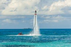 Silhueta de um cavaleiro da placa da mosca no mar O cavaleiro profissional faz truques na lagoa azul Equipamento tropical do água Imagem de Stock