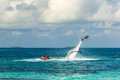 Silhueta de um cavaleiro da placa da mosca no mar O cavaleiro profissional faz truques na lagoa azul Equipamento tropical do água Fotos de Stock Royalty Free