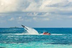 Silhueta de um cavaleiro da placa da mosca no mar O cavaleiro profissional faz truques na lagoa azul Equipamento tropical do água Imagens de Stock