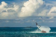 Silhueta de um cavaleiro da placa da mosca no mar O cavaleiro profissional faz truques na lagoa azul Equipamento tropical do água Imagem de Stock Royalty Free