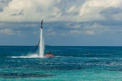 Silhueta de um cavaleiro da placa da mosca no mar O cavaleiro profissional faz truques na lagoa azul Equipamento tropical do água Fotografia de Stock