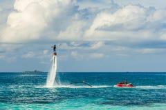 Silhueta de um cavaleiro da placa da mosca no mar O cavaleiro profissional faz truques na lagoa azul Equipamento tropical do água Foto de Stock Royalty Free