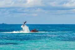 Silhueta de um cavaleiro da placa da mosca no mar O cavaleiro profissional faz truques na lagoa azul Equipamento tropical do água Fotos de Stock