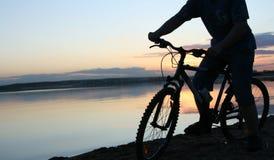 Silhueta de um ciclista no por do sol Fotos de Stock