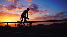 Silhueta de um ciclista no por do sol nas montanhas filme