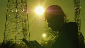 Silhueta de um coordenador no por do sol, que olha as colunas da telecomunicação O coordenador redige dados à tabuleta E filme
