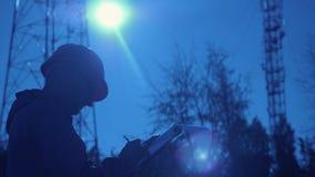 Silhueta de um coordenador no por do sol, que olha as colunas da telecomunicação O coordenador redige dados à tabuleta E video estoque