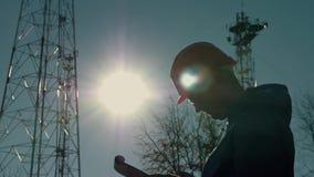 Silhueta de um coordenador no por do sol, que olha as colunas da telecomunicação O coordenador redige dados à tabuleta E vídeos de arquivo