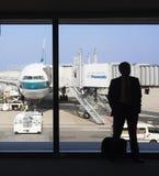 Silhueta de um embarque de espera do homem de negócios em um aeroporto Fotos de Stock Royalty Free