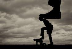 A silhueta de um grande pé pressiona em um homem que igualmente pressione seu pé em um outro homem que se encontra na terra fotos de stock