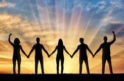 Silhueta de um grupo de povos felizes de cinco povos que guardam as mãos no por do sol fotografia de stock royalty free