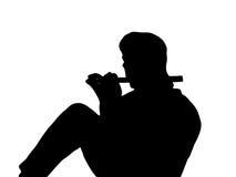 Silhueta de um homem assentado que joga uma flauta Fotos de Stock Royalty Free