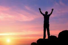 Silhueta de um homem com os braços aumentados-acima no por do sol Foto de Stock