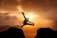 Silhueta de um homem de salto no por do sol Fotografia de Stock Royalty Free
