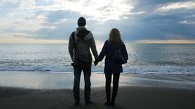 Silhueta de um homem e de uma mulher que guardam suas mãos na perspectiva do mar video estoque