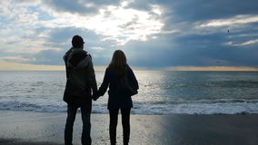Silhueta de um homem e de uma mulher que guardam suas mãos na perspectiva do mar filme