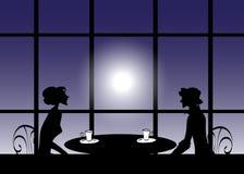 Silhueta de um homem e mulheres em uma tabela Fotografia de Stock
