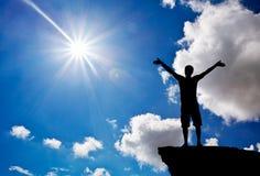 Silhueta de um homem em uma parte superior da montanha Adoração ao deus fotografia de stock royalty free