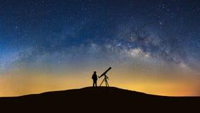 Silhueta de um homem ereto com telescópio que olha o w wilky fotos de stock