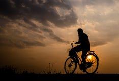 Silhueta de um homem na bicicleta no tempo crepuscular Fotografia de Stock Royalty Free