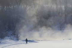 Silhueta de um homem na costa do rio congelado com névoa imagem de stock