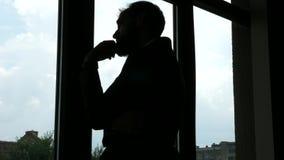 A silhueta de um homem de negócios novo incorpora o quadro então que começa olhar fora da janela e do pensamento vídeos de arquivo