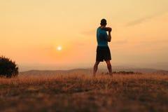 Silhueta de um homem no por do sol ao exercitar imagem de stock royalty free