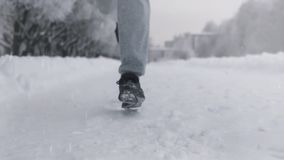 Silhueta de um homem que corre ao longo de uma estrada nevado no inverno em um parque filme