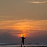 Silhueta de um homem que está no nascer do sol Imagem de Stock