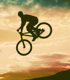 Silhueta de um homem que faz um salto com uma bicicleta do bmx Imagens de Stock Royalty Free