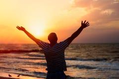 Silhueta de um homem que levanta suas mãos para o céu no por do sol na praia foto de stock