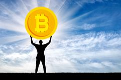 Silhueta de um homem que mantém um bitcoin da moeda contra o céu Foto de Stock Royalty Free