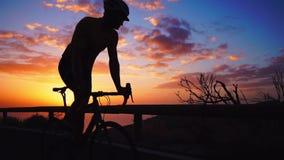 Silhueta de um homem que monta uma bicicleta no por do sol em uma opinião lateral da estrada da montanha Movimento lento Steadica filme