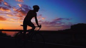 Silhueta de um homem que monta uma bicicleta no por do sol em uma opinião lateral da estrada da montanha Movimento lento Steadica video estoque