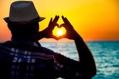Silhueta de um homem que mostra o amor com dedos fotos de stock royalty free